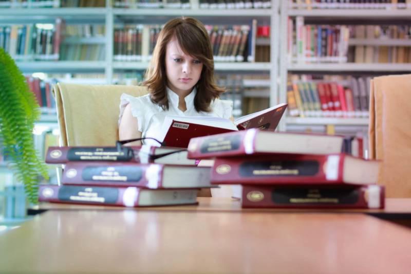Девушка готовится к экзаменам, обложившись книгами