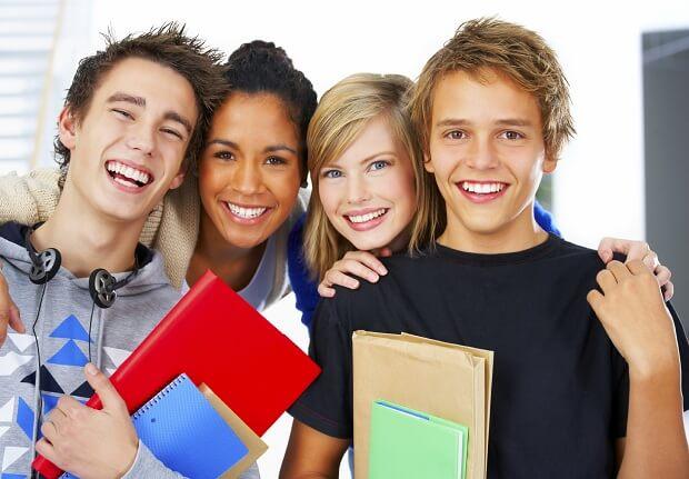Группа улыбающихся студентов - два парня и две девушки