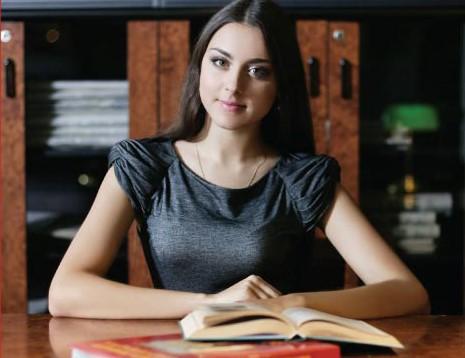 Девушка сидит за столом с раскрытой книгой