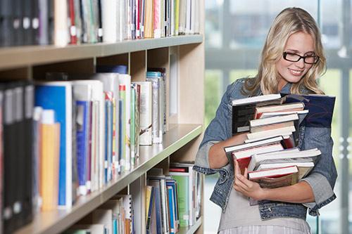 Девушка в библиотеке держит в руках стопку книг