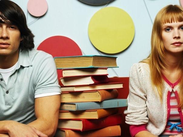 Парень и девушка сидят возле стопки с книгами
