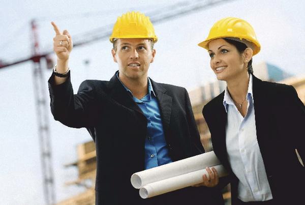Мужчина и женщина в касках на строительной площадке