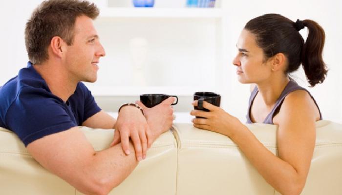 Парень и девушка пьют кофе, сидя лицом друг к другу