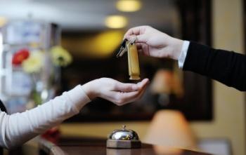 Администратор гостиницы подает ключи от номера клиенту