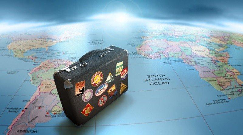 Чемодан для путешествий стоит на карте мира