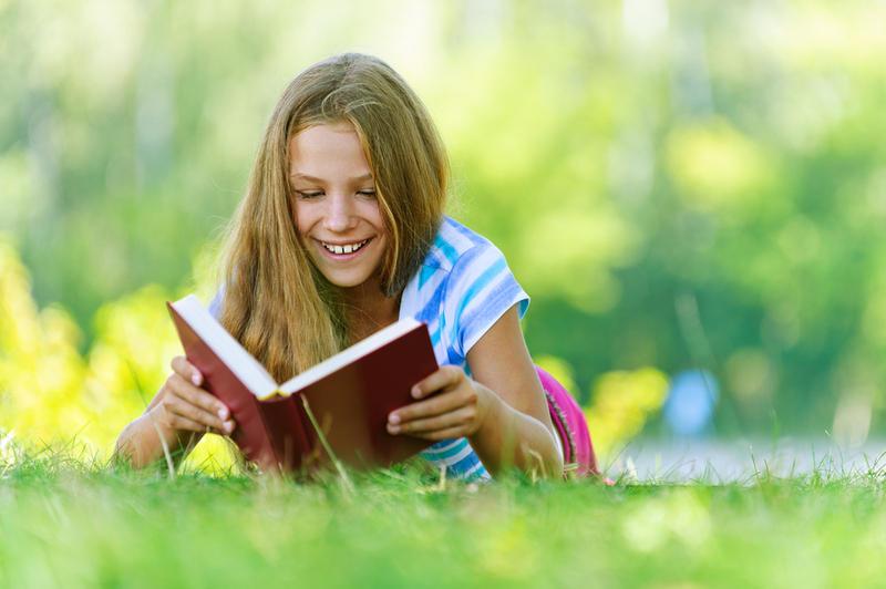 Девочка читает книгу, лежа на лужайке