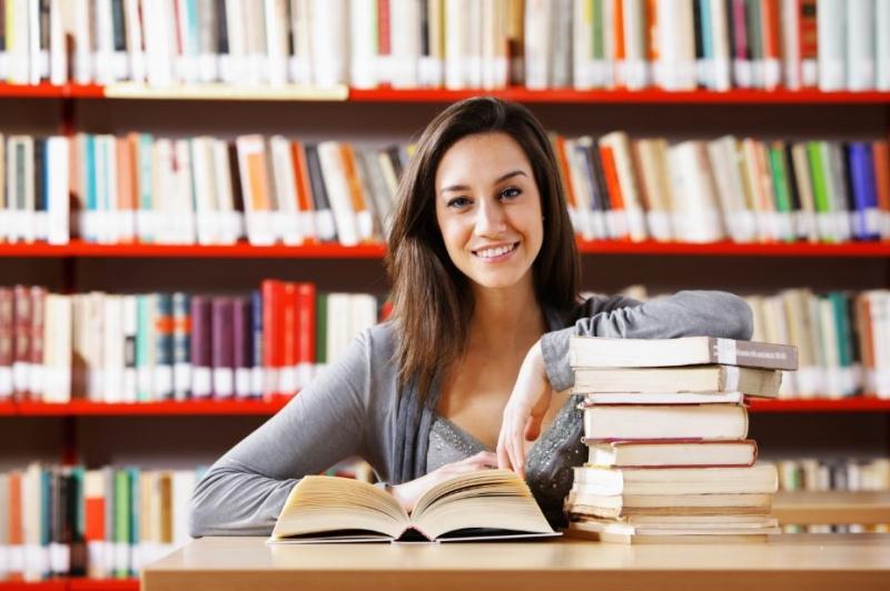 Девушка сидит в библиотеке в окружении книг