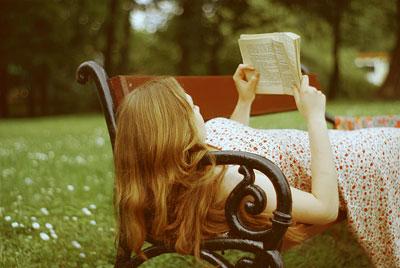 Девушка лежит на скамейке в парке с книгой