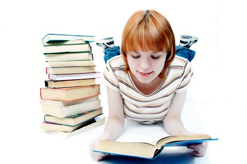 Девушка читает книгу, лежа на полу