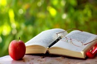Книга, очки и яблоко лежат на столе в саду