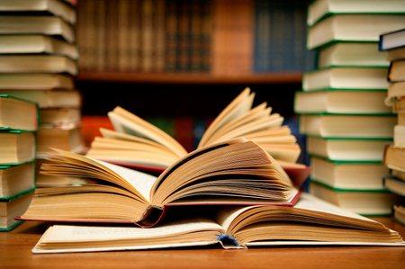 Стопки книг и раскрытые книги на столе