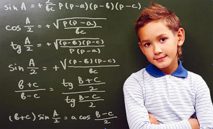 Мальчик стоит у школьной доски, на которой написаны формулы