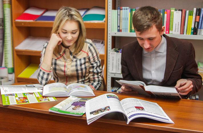 Парень и девушка рассматривают журналы