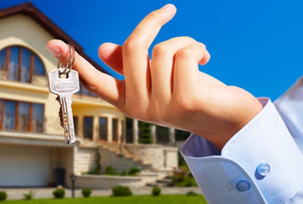 Мужчина держит в руке ключ от жилого помещения
