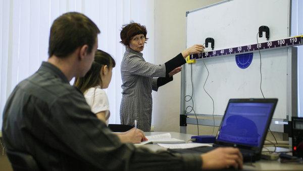 Учитель объясняет ученикам физические формулы