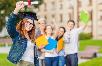 Девушка в головном уборе бакалавра позирует на фоне группы студентов