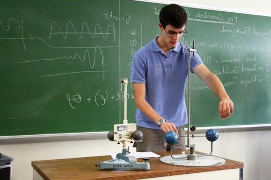 Ученик старших классов отвечает у доски на уроке физики