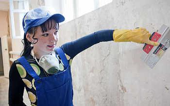 Работница штукатурит стену