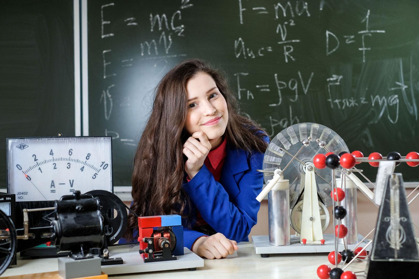 Ученица сидит за столом, на котором расположен амперметр-вольтметр и другие приборы