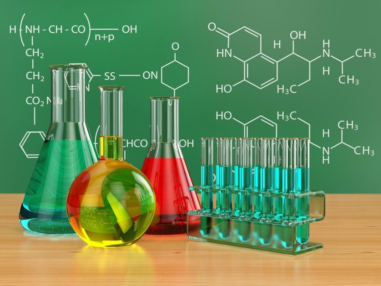 Колбы химические с растворами на фоне доски с формулами